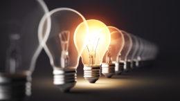 Glowing light bulb on dark background.