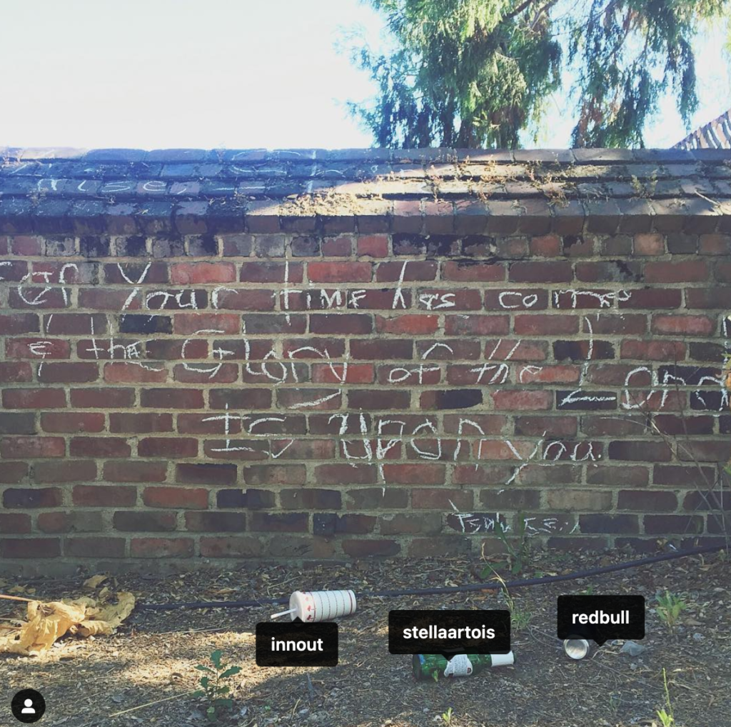 Brick wall with religious graffiti and litter on the ground.