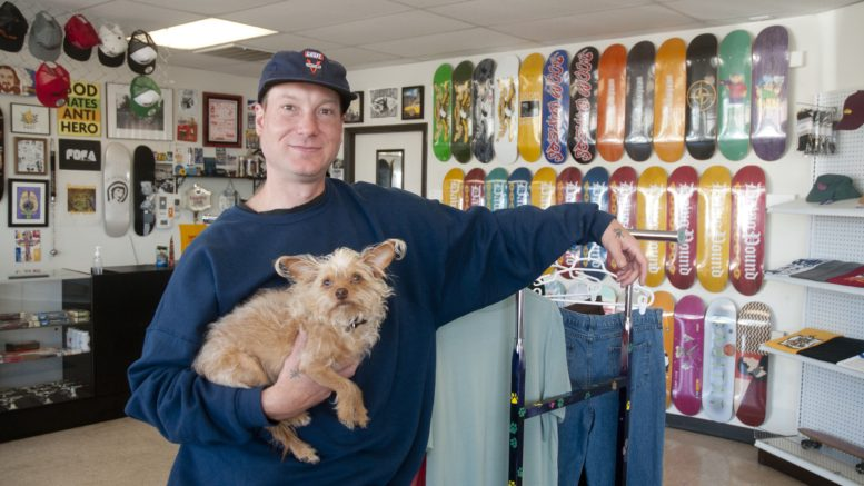 Lucas Underwood hold Ozzi the dog inside his skate shop, Dawg Pound.