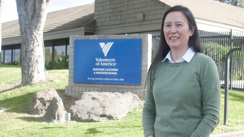Woman standing in front of Volunteers of America building